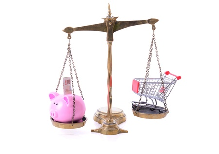 Saving on shopping concept piggy bank dn shopping cart on scales Imagens