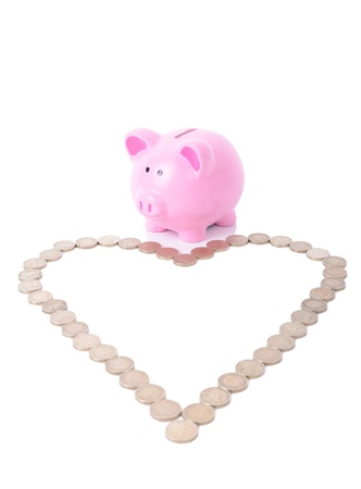 bacon love: piggy bank looking at a heart shape of coins, love money Stock Photo