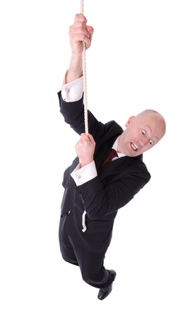 businessman hanging on the end of a rope isolated on white background