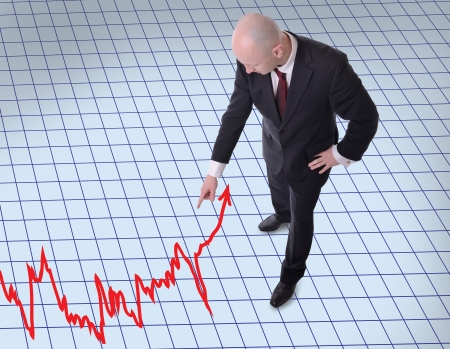 finacial: businessman pointing downwards to a graph