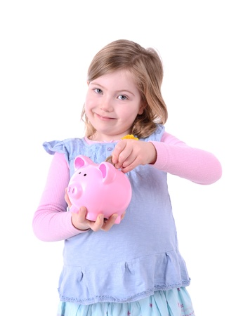 5 year old girl: young girl dropping money into a pink piggy bank isolated on white background