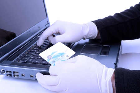 theif with protective glove online stealing with stolen credit card with a blue negitivity filter