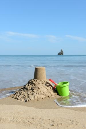 seau d eau: belle journée ensoleillée à la plage avec Château de sable, seau et pelle Banque d'images