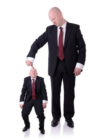 self dependent: under the thumb businessman pushing down on a businessman isolated on white Stock Photo