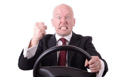 road rage: road rage behind the wheel with clenched fist isolated on white background