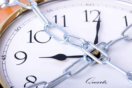 unchained: clock face chained up concept of deadline or not being late Stock Photo