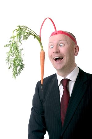 dangling: self motivation of dangling a carrot on a stick isolated on white Stock Photo