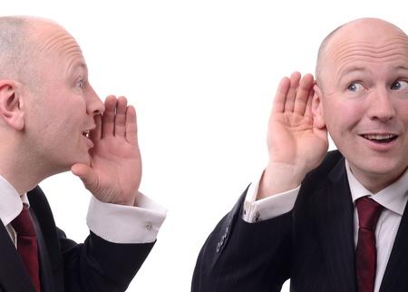 dos personas conversando: wispering informaci�n de negocios en el secreto aisladas sobre fondo blanco Foto de archivo