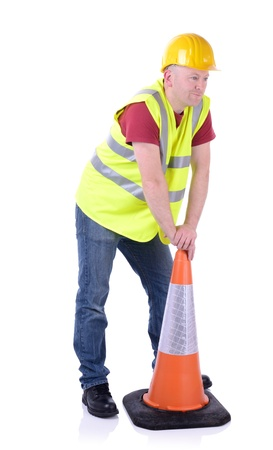 leaning by barrier: Construction worker setting out a traffic cone  isolated on white Stock Photo