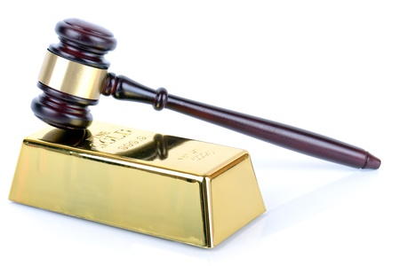 bribing: Price of gold gold bullion bar and gavel on white background