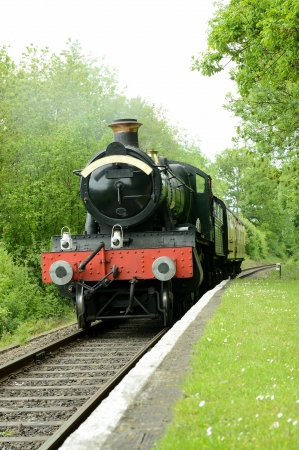 british steam train arriving at a rural platform photo