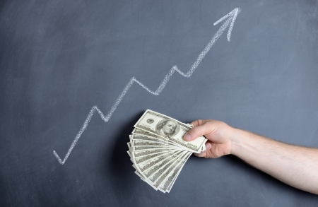 federal reserve: growth chart with a hand full of dollar bills