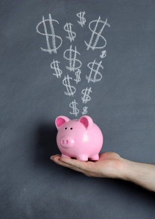 Piggy bank savings over chalkboard background photo