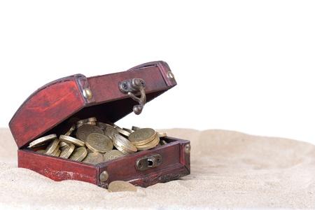 cofre del tesoro: peque�o cofre abierto con monedas de oro dentro de la parte enterrada en la arena aislado en fondo blanco