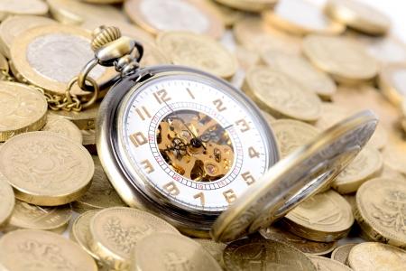 libra esterlina: Concepto de tiempo es dinero, reloj antiguo sobre un montón de monedas