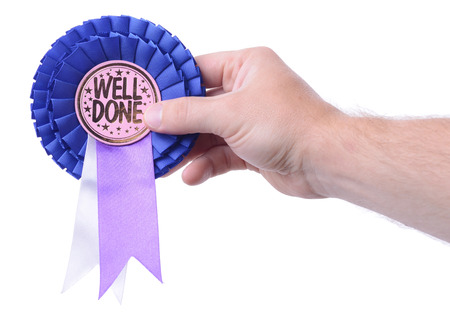 well done: a hand presenting a well done badge isolated on white