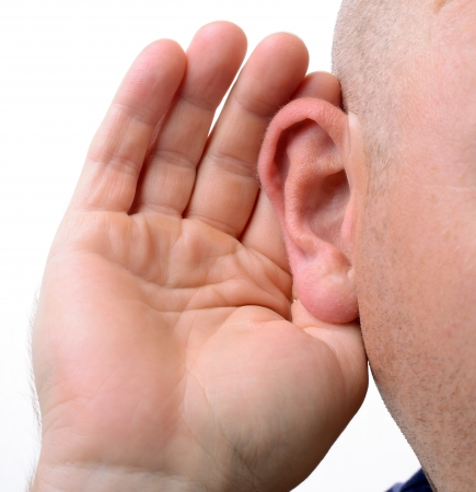 cupping: close up of a hand cupping an ear to hear better isolated on white Stock Photo