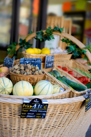 fresh fuit and vegetables in a large wovern basket in front of a small shop in france Stock Photo - 22581639
