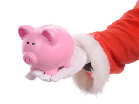 christmas savings: Sant handing out a coin piggy bank concept of christmas savings isolated on a white background Stock Photo