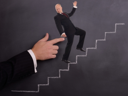 a businessman being pushed poked up stairs on a chalkboard background photo