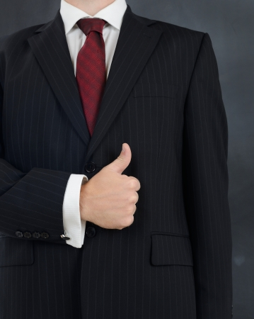 well done: man in suit giving the thumbs up sign of a good job and everthing is alright
