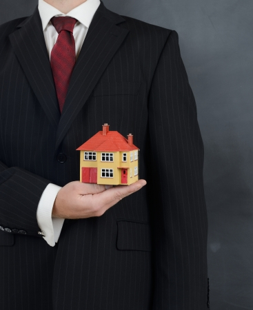 minature: man in a suit holding a minature house concept for real estate Stock Photo