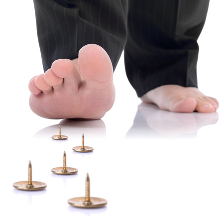 concept of unforseen problem or danger ahead, foot stepping on a pin isolated on a white background Stock Photo