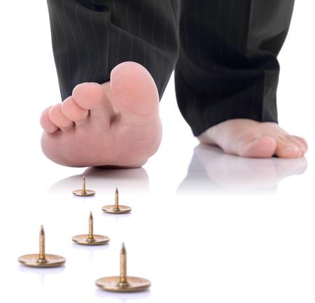 concept van de onvoorziene problemen of gevaar vooruit, voet stappen op een pin geïsoleerd op een witte achtergrond Stockfoto