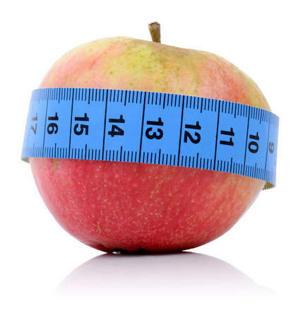 concept for healthy eating and dieting an apple with a tape measure isolated on a white bakground Stock Photo - 23080366