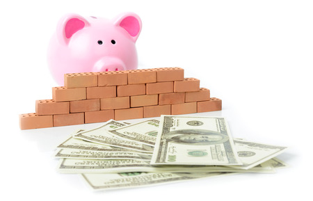 Concept of money blocked fron bank, savings with a piggy bank behind a brick wall unable to get to money. photo
