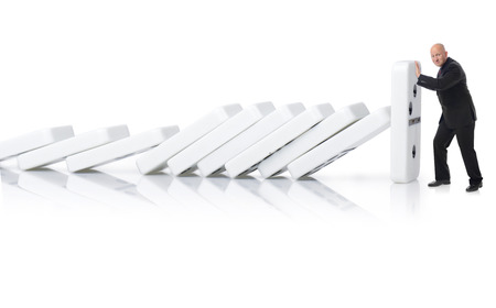 Concept of stopping a domino effect a buinessman pushing up the last peice isolated on a white background photo