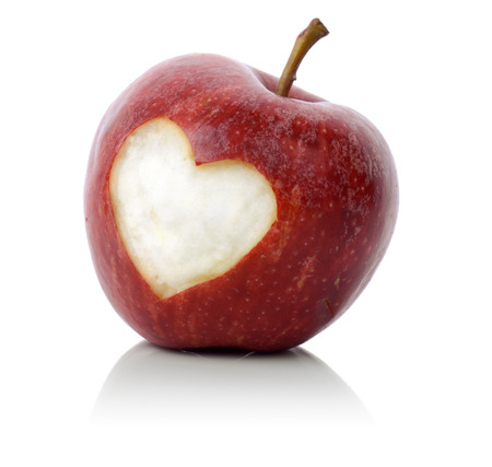 concept for loving healthy food, an apple with a heart symbol carved into it isolated on a white background Stock Photo - 23135988