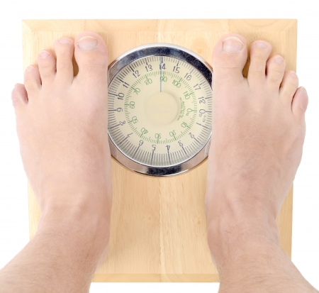 man on scales checking of progress of diet isolated on a white background Stock Photo - 23837879