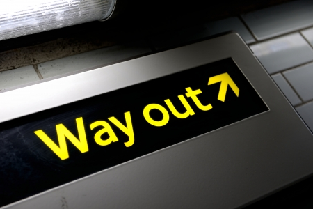 wayout: grungy way out sign from a subway in london  lit by a strip light Stock Photo