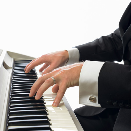 man in tuxedo playing the piano isolated on a white  photo