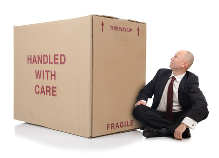 over packed: business man with packed cardboard boxes over a white background Stock Photo