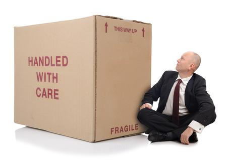 over packed: uomo di affari con i contenitori di cartone imballati sopra una priorit� bassa bianca
