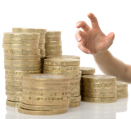 libra esterlina: Agarrando la mano por dinero aislados en un fondo blanco con la atención selectiva Foto de archivo