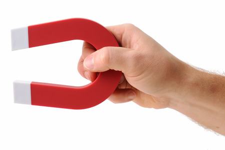 A hand holding a magnet isolated on white to pick up an object