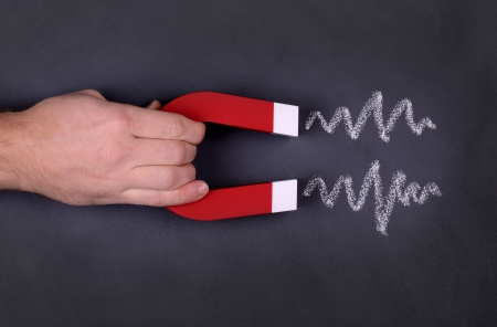 magnets: A magnet with zig zag lines showing attraction on a chalk board