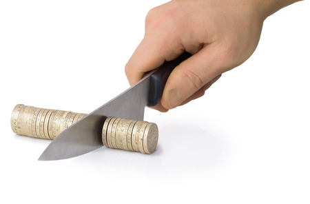 economise: knife slicing through coins, concept of cut backs or taking a cut Stock Photo