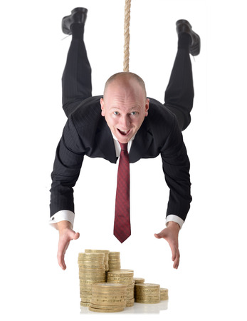 Man in suit dropping down to grab money isolated on a white background photo