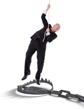Businessman hanging onto a rope fearing trap from below isolated on white