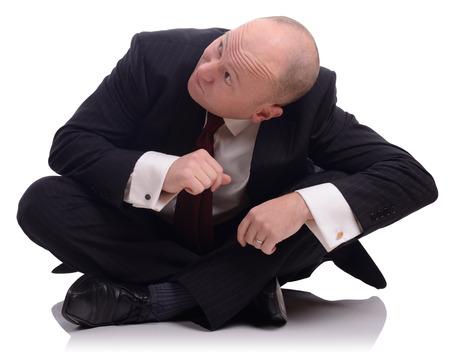 agachado: El hombre de negocios sentado en el suelo mirando hacia arriba y agach�ndose, aislado en un fondo blanco