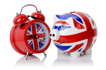 Time to make money in Britain piggy bank and alarm clock isolated on a white background photo