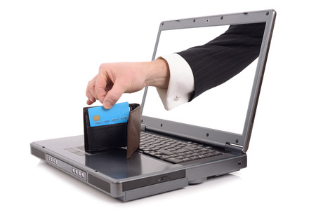 Theft over the internet concept with a hand poping out of the screen to steal a credit card, isolated on a white background
