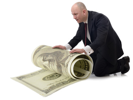 taking care of money a man rolling up a large 100 dollar bill isolated on a white background. photo
