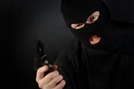 ski mask: terrorist in a ski mask holding a gun with a dark background