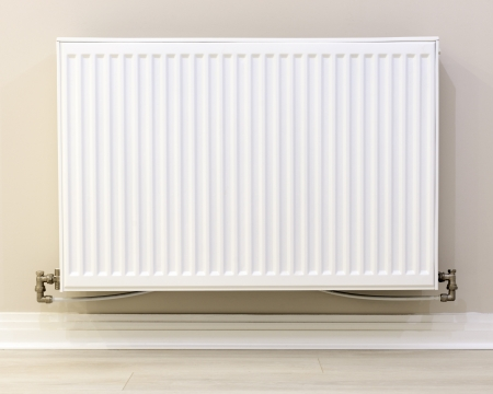 radiator: full view of a white radiator  against a cream wall