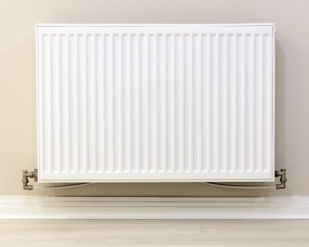 radiador: la vista de un radiador blanco contra una pared de crema